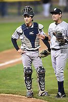 Staten Island Yankees catcher Luis Torrens (57) and third baseman Renzo Martini (33) look on as coach Luis Figueroa (not shown) argues a call with umpire Justin Houser (not shown) during a game against the Batavia Muckdogs on August 7, 2014 at Dwyer Stadium in Batavia, New York.  Staten Island defeated Batavia 2-1.  (Mike Janes/Four Seam Images)