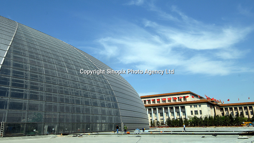 "Some of the final ground-work and land-scaping is carried out at the new National Grand Theatre, locally known as ""duck egg"", designed by French architect Paul Andreu. The  building will open before the 2008 Beijing Olympics. .01 May 2007"