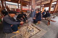 Asia,Cina ,Guizhou,Chengyang, old Dong men smoke pipe around the fire ,China minority