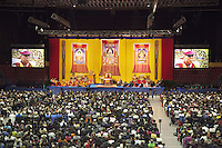 """Switzerland. Basel. St. Jakobshalle. The audience listens to His Holiness the Dalai Lama who is on stage during a public lecture on Bodhicitta. The topic of his talk is about Nagarjuna's Commentary on Bodhicitta which touches on two aspects of the awakening mind, the twin qualities of wisdom and compassion, which are necessary for anyone who aspires to be a better person and implement changes in their lives. The 14th and current Dalai Lama is Tenzin Gyatso, recognized since 1950. He is the current Dalai Lama, as well as the longest-lived incumbent, well known for his lifelong advocacy for Tibetans inside and outside Tibet. Dalai Lamas are amongst the head monks of the Gelug school, the newest of the schools of Tibetan Buddhism. The Dalai Lama, also called """" Ocean of Wisdom"""" is considered as the incarnation of Chenresi, the Bodhisattva of compassion who is also the protective deity of Tibet. 7.02.2015 © 2015 Didier Ruef"""