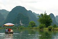 Chinese couple rowing a bamboo raft along the Yulong River with a European family on board, Yangshuo, Guangxi, China.