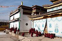 Tibetan monks outside the Upper Wutan Monastery, Rebgong (Chinese name - Tongren),  on the Qinghai-Tibetan Plateau. China.