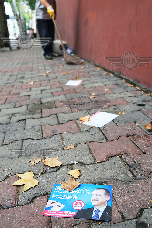 Electoral flyers with images of president Recep Tayyip Erdogan lie on a side road pavement where they are about to be swept up by a street cleaner.
