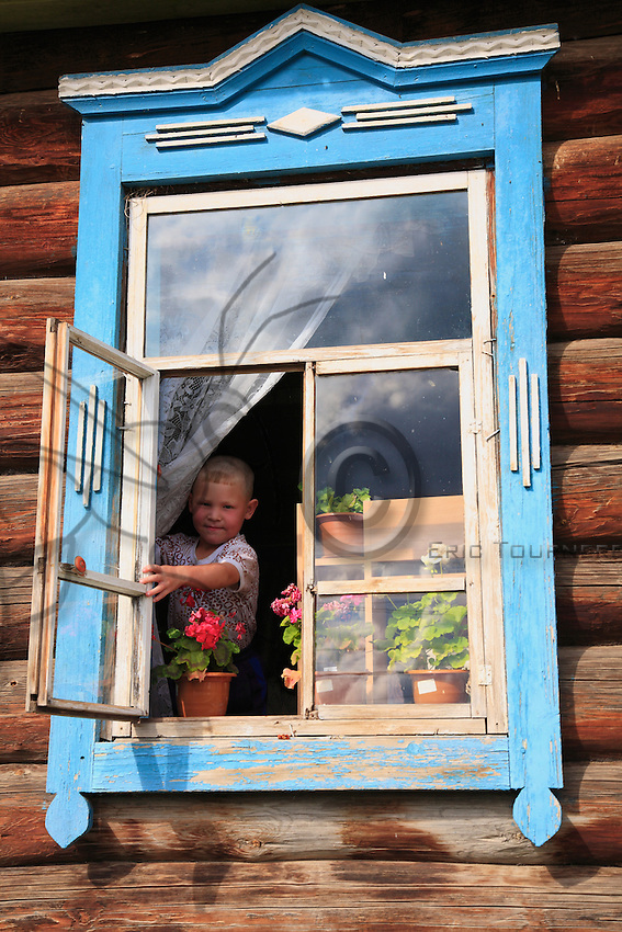 Child gazing through a window of sculpted wood adorned with white curtains and flowerpots.