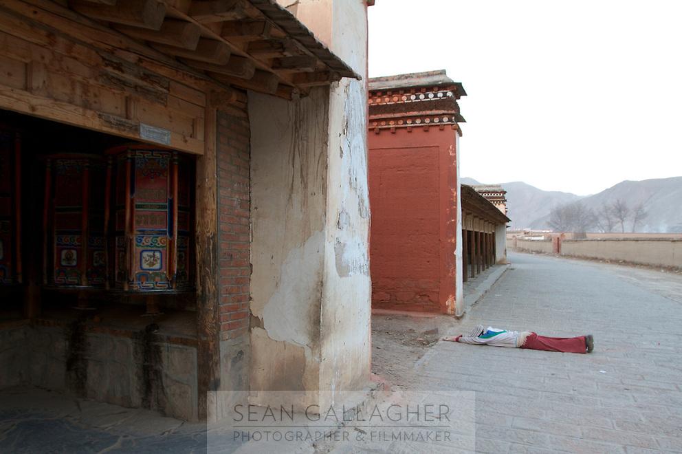 A Tibetan pilgrim prostrates at Labrang (Chinese Name - Xiahe) Monastery on the Qinghai-Tibetan Plateau. China.