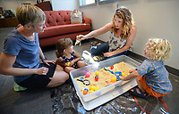 """Bethany White (top right) of Winslow shows a plastic dinosaur Tuesday, July 27, 2021, to Sophie Jett, 3, and her mother, Trish Jett (left) of Winslow while playing in a """"dinosaur dig"""" with White's son, Axyl White, 2, (right) at the West Fork Public Library's Summer Reading Finale at the library. Participants enjoyed games, bubbles and treats. Visit nwaonline.com/210728Daily/ for today's photo gallery.<br /> (NWA Democrat-Gazette/Andy Shupe)"""