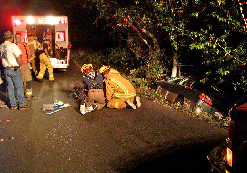 Firefighters treat the victim of a single vehicle accident as paramedics arrive in Occidental California.  The car slid off the road into a ditch at night.