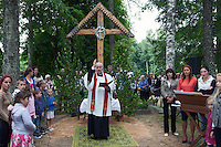 Karsava, Latvia, 21/07/2013.<br /> A priest conducts a religious service in the cemetery and blesses graves in the village of Karsava, near the Russian border.