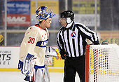 Rochester Amerks goalie Matt Hackett (30) talks to linesman Jeff Walker (28) after allowing a goal with .01 seconds left in the third period of The Frozen Frontier outdoor AHL game to force overtime against the Lake Erie Monsters at Frontier Field on December 13, 2013 in Rochester, New York.  (Copyright Mike Janes Photography)