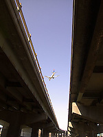 Airplane landing, photographed sandwiched between highway overpasses<br />