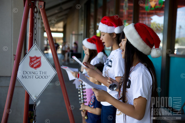 Local youth wearing Santa hats sing Christmas carols for the Salvation Army outside of Longs Drugs store in Kahalui, Maui.