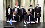 Palestinian Prime Minister Mohammed Ishtayeh signs the support agreement worth $ 20 million for digital infrastructure project, in the West Bank city of Ramallah, on April 8, 2021. Photo by Prime Minister Office