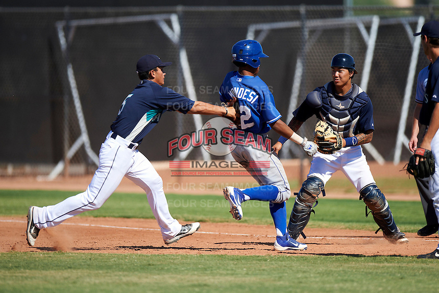 Seattle Mariners minor league infielder Timmy Lopes #5 tags out Raul Mondesi #22 in a rundown as catcher Christian Carmichael #15 looks on during an instructional league game against the Kansas City Royals at the Peoria Sports Complex on October 2, 2012 in Peoria, Arizona.  (Mike Janes/Four Seam Images)