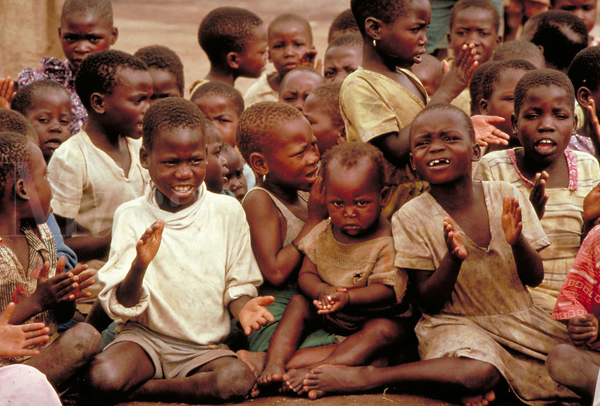 African children singing Christian songs in a refugee camp in Malawi, Africa.  Most of them are orphans as a result of civil wars in the area (1993), child, victims of war, violence. African children in camp. Malawi Africa refugee camp for children.