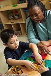 Preschool 3-4 year olds female teacher and boy working together, boy building with magnetic blocks