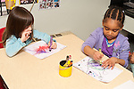 Education Preschool Headstart 3-4 year olds two girls sitting near each other art activty both drawing with crayons using opposite hands