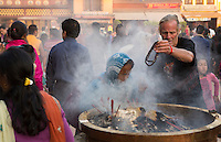 Kathmandu Nepal Man and old woman praying in incense pot at the Boudhanath Stupa 2 3