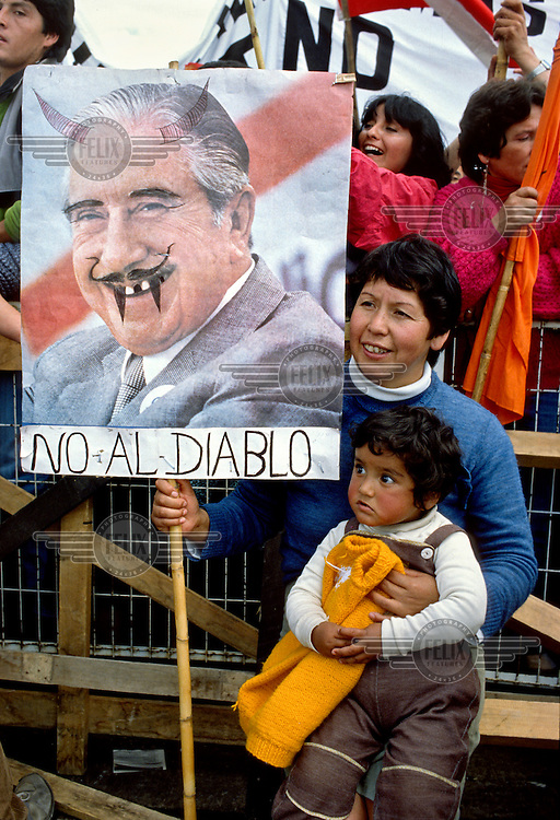 A mother, with her child on her knee, during a rally called by those campaigning for a 'No' vote in the 1988 referendum. This asked the people to choose either 'Yes' for a continuation of Pinochet's rule or 'No' for him to leave office. The woman holds a placard with a photograph of Pinochet that has had 'devil's' features drawn on it and the slogan 'No to the Devil' written beneath.