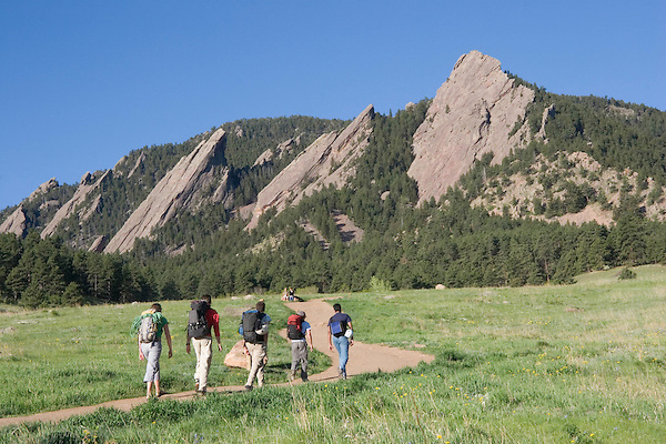 Caucasian male and female hikers and rock climbers, Flatirons rock formation, Chautauqua Park, Foothills, Boulder, Colorado, USA .  John leads private photo tours in Boulder and throughout Colorado. Year-round.