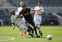 LOS ANGELES, CA - APRIL 17: Carlos Vela #10, of LAFC battles with  Jhohan Romaña  #3 and Daniel Pereira #15 of Austin FC during a game between Austin FC and Los Angeles FC at Banc of California Stadium on April 17, 2021 in Los Angeles, California.