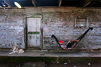 Man relaxing on his porch while talking on the phone. Jaque, Panama.