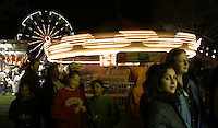 From right, Aurora Nichols waits in line for funnel cake with friend Yasmina Mrabet during the annual Dogwood Festival Tuesday night at McIntire Park in Charlottesville, Va. Photo/The Daily Progress/Andrew Shurtleff ride carnival