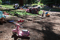 Italy. Lombardy Region. Como. Homeless african migrants living in the park below the San Giovanni railway station. Men sleep on the ground in the afternoon. Toys for children: a pink Vespa, a tricycle, a doll and a red stuffed animal. The trash can is full with garbage. Several pink  plastic bags are full of waste and lie on the ground. 10.08.2016 © 2016 Didier Ruef