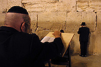 """An Orthodox Jew pries """"Selihot"""" or special prayers for forgiveness at the Western Wall in the Old City of Jerusalem, September 10,2002. According to Jewish tradition in this prayers the Jew asks the Lord for forgiveness for all sins and omissions in connection with religious observance, during the hours after midnight till the daybreak.  Tradition marks the days after Rosh Hashanah and before the Day of Atonement, Yom Kippur, as most appropriate to ask for forgiveness. Photo by Quique Kierszenbaum"""