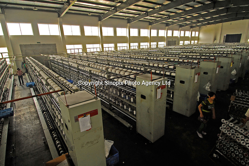 """The spinning room at Taiming Chemical Fibre Limited in """"Datang Sock Town"""" in Zhuji City Zhejiang Province, China. The  factory, one of several spinning factories,  runs 24 hours a day producing over 100,000 spools of nylon yarn per day which are all consumed in Datang Town. The town makes more than 5.3 billion pairs of socks annually - that 2.5 pairs for every human alive.  Most people in the town make a living directly connected to the sock weaving industry..14 Jun 2006"""