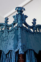 Detail of the carved crest of a Chippendale state bed, intricately covered in blue silk