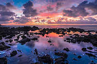 Sunrise over Pacific Ocean and volcanic rocks with puddle reflection, in Bora Bora, beautiful honeymoon destination, near Tahiti, French Polynesia