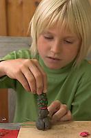 Kinder basteln Zwergengärtchen, Zwergen-Gärtchen aus Naturmaterialien, Bastelei, ein Zwerg wird aus Ton und Zapfen gebastelt