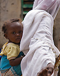 Haoua Pendooru, a Fulani woman in Ouagadougou, Burkina Faso, walks past the camera with her toddler on her back, in traditional African fashion.