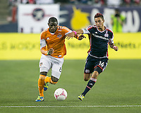 Houston Dynamo defender Kofi Sarkodie (8) dribbles the ball down the wing as New England Revolution midfielder Diego Fagundez (14) gives chase.  The New England Revolution played to a 1-1 draw against the Houston Dynamo during a Major League Soccer (MLS) match at Gillette Stadium in Foxborough, MA on September 28, 2013.