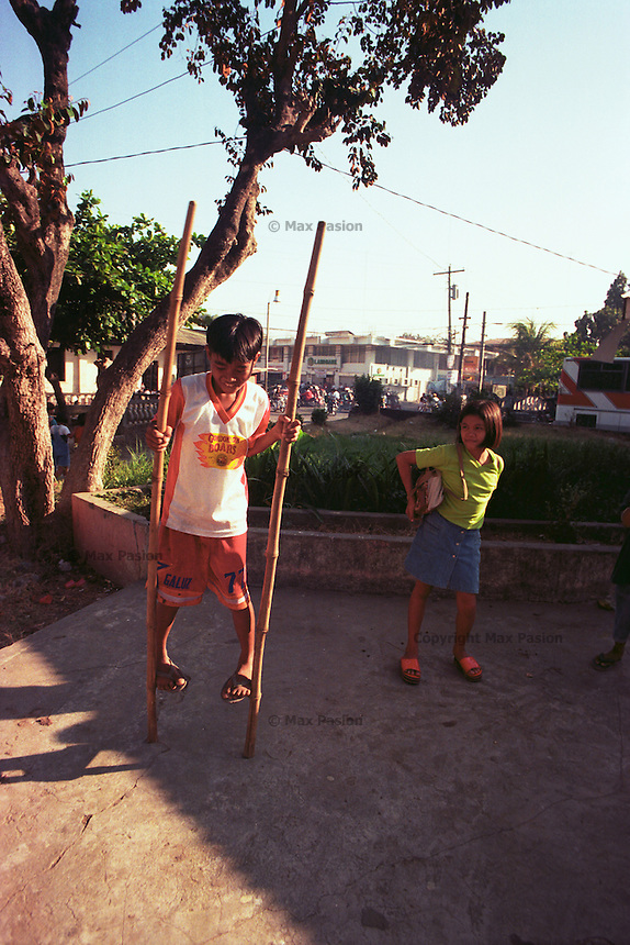 Boy impresses girl with his stilt walking. Bangued, Abra. March, 1998