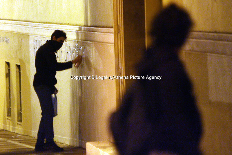 """Pictured: A protester spraying a graffiti reading """"Support to Nikos Romanos"""" on a building wall in AThens, Greece Tuesday 02 December 2014<br /> Re: At least 15 people have been arrested after a peaceful support rally for jailed hunger strike anarchist turned into violent confrontation with police. Authorities used tear gas and stun grenades to quell rioters carrying Molotov cocktails.<br /> As an estimated between 8,000 and 10,000 protesters marched through the central Athens shouting slogans in support of Nikos Romanos, the imprisoned anarchist who is staging a hunger strike as he demands the right to be able to attend university, anarchists' march got violent on the streets of Exarchia, downtown Athens."""