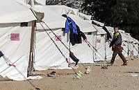 Pictured: A boy walks by a row of tents Friday 26 February 2016<br /> Re: Hundreds of refugees have been given temporary shelter at the Stefanakis Army Camp in the Schisto area of Athens, Greece.