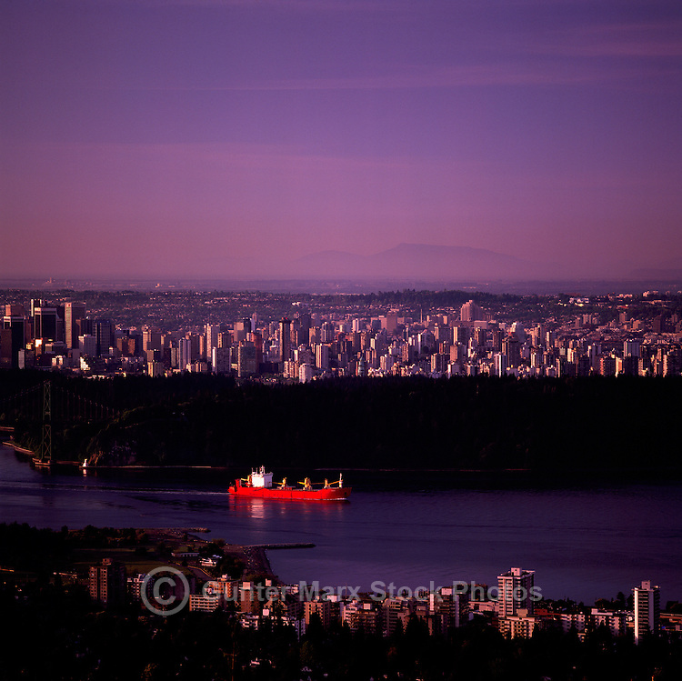 Vancouver, BC, British Columbia, Canada - Freighter leaving Port of Vancouver at Sunrise. City of North Vancouver in foreground, City of Vancouver in background, behind Stanley Park.