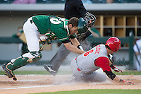 Charlotte 49ers catcher Nick Daddio (20) loses his mask as he applies the tag to Logan Ratledge (6) of the North Carolina State Wolfpack at BB&T Ballpark on March 31, 2015 in Charlotte, North Carolina.  The Wolfpack defeated the 49ers 10-6.  (Brian Westerholt/Four Seam Images)