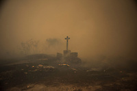 A cross from a grave is seen through smoke of wildfire in Lucenza, in Cualedro, near Ourense on August 30. A fire broke out on August 30, 2015 around noon in the Cualedro town in Galicia, northwest Spain, affecting at least 3,180 hectares of forest, as seven fires continued to burn in Spain, three in Galicia, one in Cantabria, one in Castile and Leon, one in Catalonia and Extremadura. © Pedro ARMESTRE