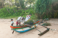 Sinhalese (Buddhist) family readys the outrigger canoe and nets for the day -Beruwala, Sri Lanka