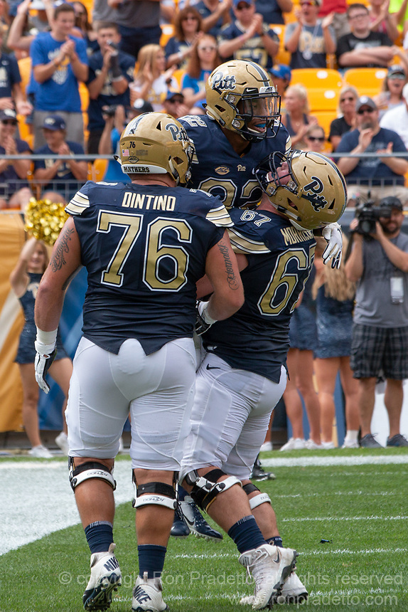 Pitt offensive linemen Connor Dintino (76) and Jimmy Morrissey (67) celebrate with running back Darrin Hall after Hall's 5-yard touchdown run. The Pitt Panthers football team defeated the Georgia Tech Yellow Jackets 24-19 on September 15, 2018 at Heinz Field in Pittsburgh, Pennsylvania.