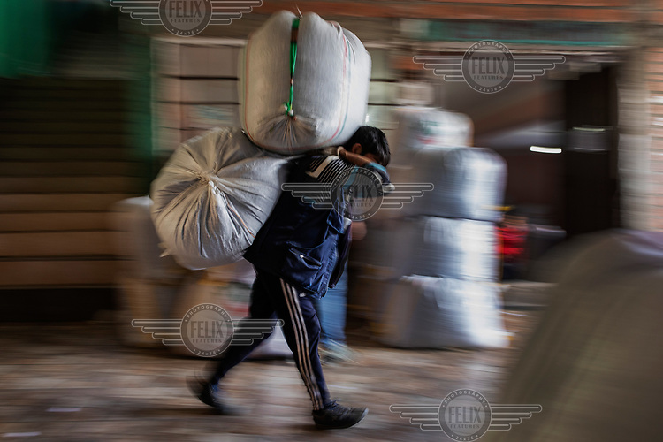 A porter carries sacks of coca leaves at the coca market in the Villa Fatima neighbourhood.<br /><br />Former President and former coca farmer Evo Morales, forced the American DEA to leave Bolivia and introduced a policy of legal coca farming while maintaining strong enforcement of drug laws to combat the illegal production of cocaine. As a consequence the area under coca production has remained constant and the murder rate in Bolivia remains one of the lowest in Latin America. The Bolivian experience is at odds with the other two major producers Colombia and Peru which have had little success in suppressing coca production which continues to expand, while murder rates in both countries remains high.