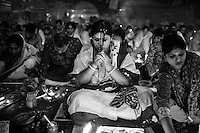 """During Kartik, """"the holiest month"""" beginning every year with the new moon in November, thousands of Hindu devotees celebrate the feast of Rakher Upobash, fasting and praying the gods sitting before the Shri Shri Lokanath Brahmachari Ashram, among the Swami Bagh Temple near Dhaka, Bangladesh. The worshippers offer candles called Prodip, meditate, give to charity, and generally perform austerity. Devotees women prepare for the celebration. Barodi, Dhaka, Bangladesh. Nov. 11, 2014"""