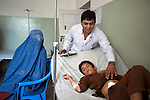 5 June 2013, Kholm District Hospital, Mazar-i-Sharif, Balkh Province, Afghanistan.    Eight year old Shafiullah lies on his bed recovering from an appendix operation performed by Dr Saber Zahier at the Kholm District Hospital outside Mazar-i-Sharif. His mother Tangi-Tash Qhoran waits with him. The hospital which has 54 beds and before 2004 was only a clinic is funded by the Strengthening Health Activities for Rural Poor Project (SHARP). SHARP aims to improve the health and nutrition status of Afghans, focusing especially on women and children and the underserved areas of the country. Already remarkable progress has been made in the reduction of infant and under five mortality as well as pregnancy related mortality. With World Bank support in 11 provinces the number of health clinics has nearly tripled from 148 to 432 and about 85% of the population now lives in districts which now have service providers to deliver a basic package of health service.  The project supports Afghanistan's Health and Nutrition Sector Strategy  which is the governments blueprint for the health sector program for the period 2008-13. Picture by Graham Crouch/World Bank.