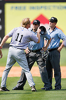 Jacksonville Suns manager Tim Leiper #11 argues a call with first base umpire Sean Barber as home plate umpire Gerard Ascani intervenes at Five County Stadium May 16, 2010, in Zebulon, North Carolina.  Photo by Brian Westerholt /  Seam Images