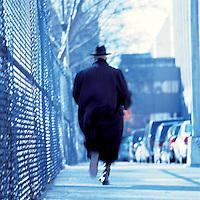 Man in coat running away from camera