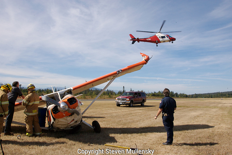 The pilot of this 1947 Stinson is being airlifted by a medical helicopter to a hospital for treatment of injuries suffered when a wind gust blew the plane off the runway while landing at Jefferson County International Airport in Port Townsend, Washington. The plane dug a wing into the dirt and cartwheeled before coming to rest. The pilot was treated at the hospital and released later in the day.