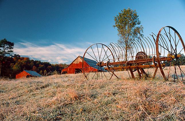 Hayrake in pasture with barn