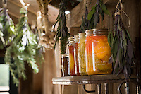 Food storage - jars of canned preserves on shelf in country living barn with bunches of dried herbs